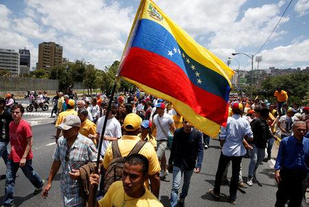 Opposition supporters holding a Venezuelan flag  protest against Venezuela's President Nicolas Maduro's government during a rally in Caracas