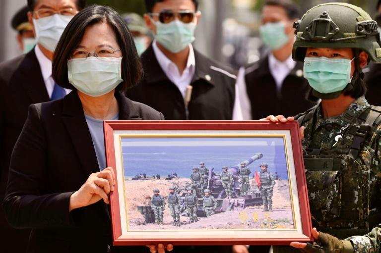 Taiwan President Tsai Ing-wen receives a framed photograph from a masked soldier during the COVID-19 coronavirus pandemic during a visit to a military base in Tainan on April 9, 2020 (AFP Photo/Sam Yeh)
