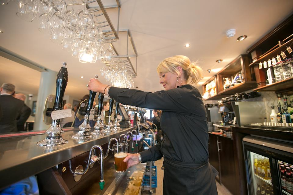 Barmaid Rochelle Chapman pulls a pint of ale at the new JD Wetherspoon pub the Hope and Champion which has opened at the M40 Services at Beaconsfield, Buckinghamshire.   (Photo by Steve Parsons/PA Images via Getty Images)