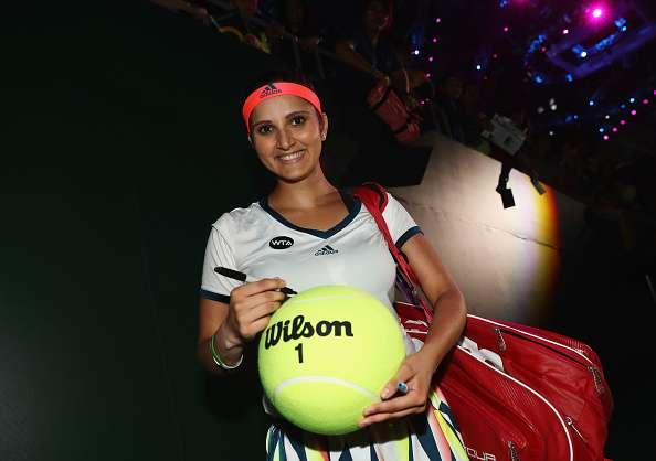 SINGAPORE - OCTOBER 28: Sania Mirza of India signs a tennis ball after partnering Martina Hingis of Switzerland in their doubles match against Hao-Ching Chan and Yung-Jan Chan of Republic of China during day 6 of the BNP Paribas WTA Finals Singapore at Singapore Sports Hub on October 28, 2016 in Singapore. (Photo by Julian Finney/Getty Images)
