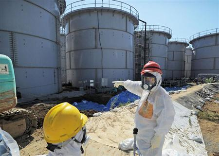 Japan's Economy, Trade and Industry Minister Toshimitsu Motegi (R), wearing a protective suit and a mask, inspects contaminated water tanks at the tsunami-crippled Fukushima Daiichi nuclear power plant in Fukushima prefecture August 26, 2013, in this photo released by Kyodo.