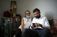 Elie Hasrouty waits with his mother Ibtissam for news of his father Ghassan Hasrouty, a missing silo employee, following Tuesday's blast in Beirut's port area