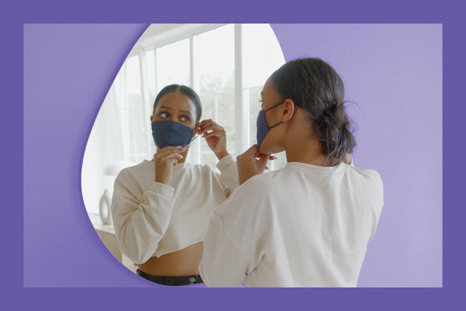 maskitis , What to Do If Your Face Mask Is Causing a Rash , Black African American female puts on a protective face mask before leaving her apartment. COVID-19 pandemic, preventive measures of coronavirus