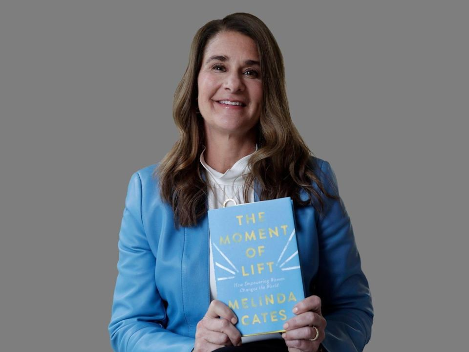 "Melinda Gates poses with her  book, ""The Moment of Lift,"" graphic element on gray"