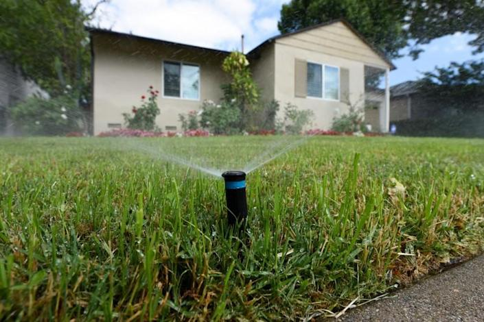 Sprinklers water the front lawn of a house on Zelzah Avenue in Encino.