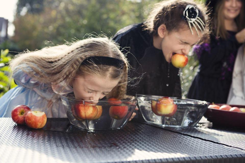 """<p>Answer: Bobbing for apples actually began as an <a href=""""https://bestlifeonline.com/cool-halloween-facts/"""" rel=""""nofollow noopener"""" target=""""_blank"""" data-ylk=""""slk:18th-century dating ritual"""" class=""""link rapid-noclick-resp"""">18th-century dating ritual</a>. According to the History Channel, <a href=""""https://www.history.com/news/what-is-bobbing-for-apples"""" rel=""""nofollow noopener"""" target=""""_blank"""" data-ylk=""""slk:certain apples would be assigned to different suitors"""" class=""""link rapid-noclick-resp"""">certain apples would be assigned to different suitors</a> and women would try to bite on to the apple they preferred. <br></p>"""