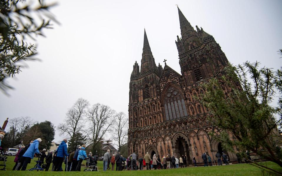 Members of the public queue outside Lichfield Cathedral, Staffordshire, to receive an injection of the Oxford vaccine - Jacob King/ PA