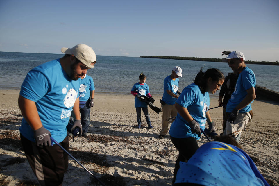 People gather trash on the beach for the Huddle for 100 beach clean up at the Historic Virginia Key Beach Park on Tuesday, Jan. 28, 2020, in Miami. Climate change poses a threat to South Florida's way of life, including Miami's customary spot in the NFL's Super Bowl rotation. The game will be played Sunday in Miami for the 11th time, the most of any city. But the sea and temperature are rising, which could eventually make South Florida an unsuitable Super Bowl site. (AP Photo/Brynn Anderson)