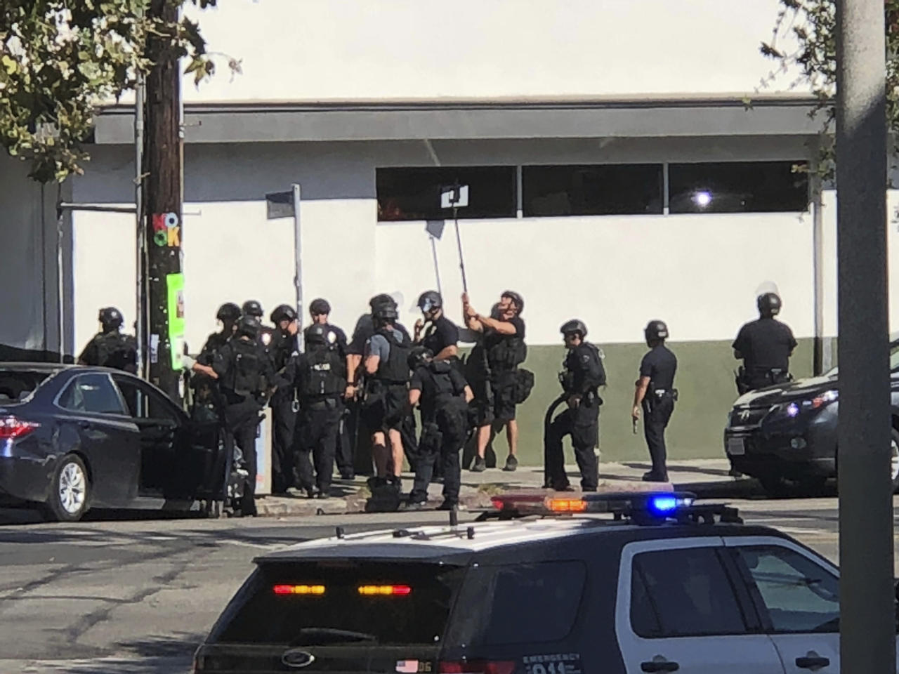 <p>Police officers use a mirror to see inside a Trader Joe's store in the Silver Lake neighborhood of Los Angeles on Saturday. Police believe a man involved in the standoff with officers shot his grandmother and girlfriend before firing at officers during a pursuit, then crashing outside the supermarket and running inside the store. (Photo: Christian Dunlop via AP) </p>