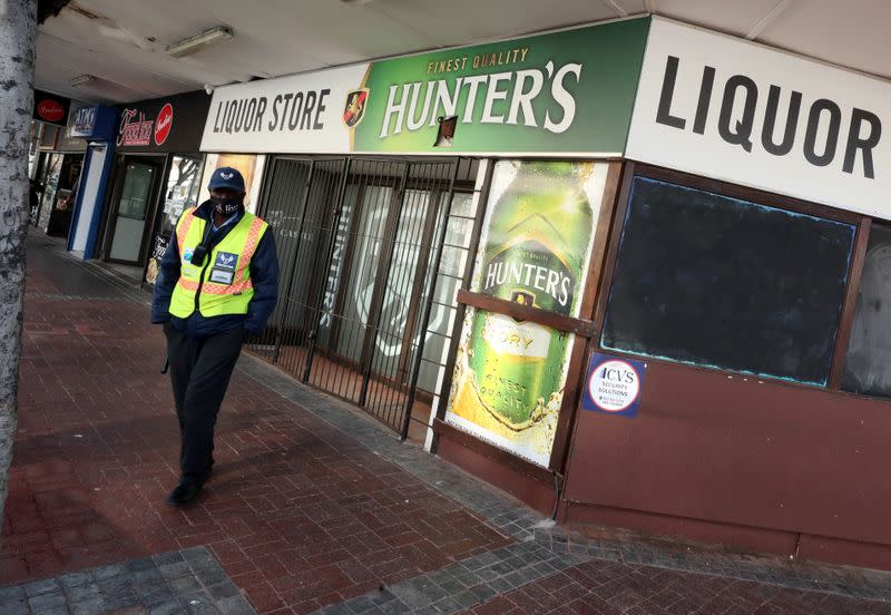 A security guard stands outside a liquor store closed under the coronavirus disease (COVID-19) lockdown regulations in Cape Town