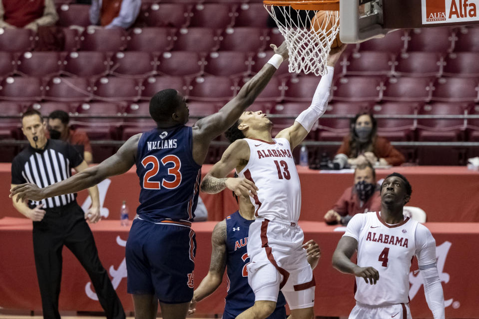 Alabama guard Jahvon Quinerly (13) gets past Auburn forward Jaylin Williams (23) for a basket during the second half of an NCAA college basketball game, Tuesday, March 2, 2021, in Tuscaloosa, Ala. (AP Photo/Vasha Hunt)