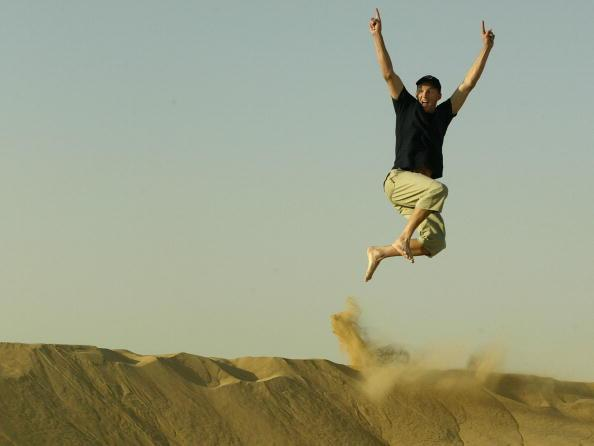 SHARJAH - OCTOBER 15:  Brett Lee of Australia leaps off a sand dune during a team visit to Wonder Desert in United Arab Emirates on October 15, 2002. (Photo by Hamish Blair/Getty Images)