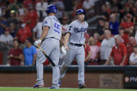 Los Angeles Dodgers' Will Smith, right, slaps hands with Albert Pujols after scoring a run during the ninth inning of the team's baseball game against the Cincinnati Reds in Cincinnati, Friday, Sept. 17, 2021. The Reds won 3-1. (AP Photo/Aaron Doster)