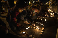 Children light candles as people gather for Kevin Peterson Jr., who was killed in Thursday's shooting with police involved, at a candlelight vigil in Vancouver, Wash., Friday, Oct. 30, 2020. The Clark County Sheriff's office has not released any details on the Thursday evening shooting in Hazel Dell, but a man told The Oregonian/OregonLive that his 21-year-old son was fatally shot by police. (AP Photo/Paula Bronstein)