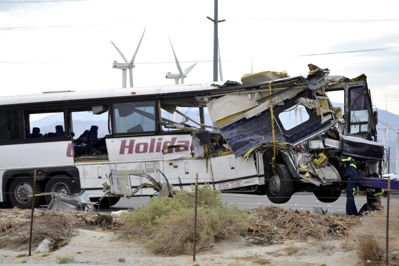FILE - In this Oct. 23, 2016, file photo, workers prepare to haul away a tour bus that crashed with semi-truck on Interstate 10 just west of the Indian Canyon Drive off-ramp, in Desert Hot Springs, near Palm Springs, Calif.  Officials say Bruce Guilford, a trucker who fell asleep behind the wheel was sentenced, Friday, Aug. 30, 2019,  to four years in state prison after he pleaded guilty to causing a tour bus crash on a Southern California freeway that killed 13 people in 2016. (AP Photo/Rodrigo Pena, File)