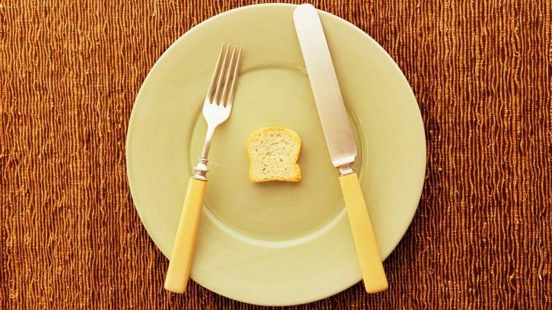 Tiny toast on big plate with fork and knife