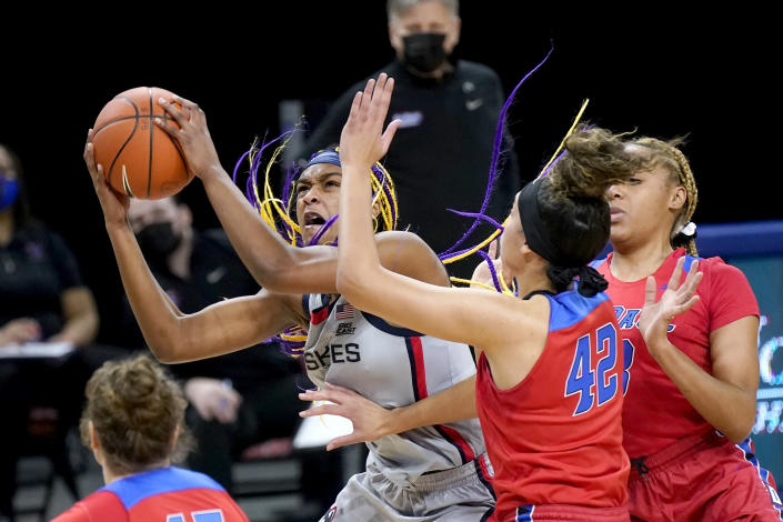 Connecticut's Aaliyah Edwards, left, drives to the basket past DePaul's Kiara Dallmann (42) during the first half of an NCAA college basketball game Sunday, Jan. 31, 2021, in Chicago. (AP Photo/Charles Rex Arbogast)
