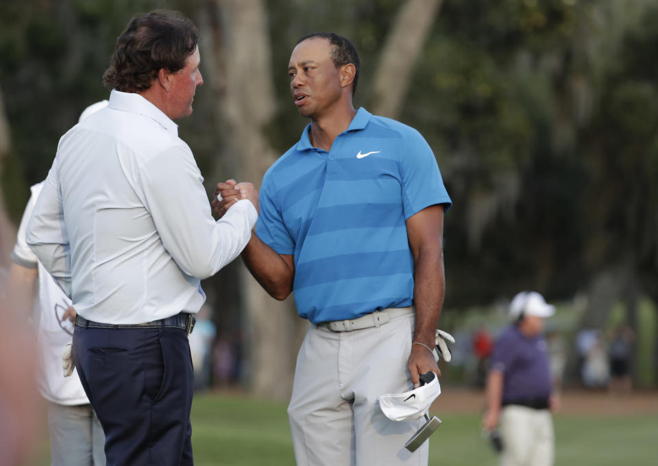 Phil Mickelson, left, shakes hands with Tiger Woods in May. Next, they'll be playing for $10 million (AP Photo/Lynne Sladky)
