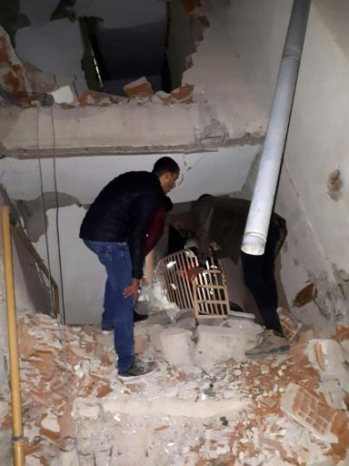 Men stand on rubble of a collapsed building after a 6.8 magnitude earthquake in Elazig, eastern Turkey on January 24, 2020, killing several people; The quake shook the Sivrice district in the eastern province at around 8.55 pm (1755 GMT)