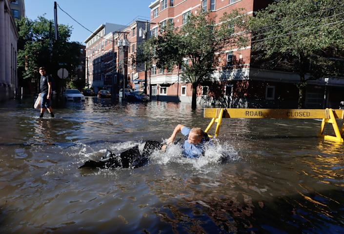 A man in Hoboken, N.J., falls off his bike into a flooded street on Thursday.
