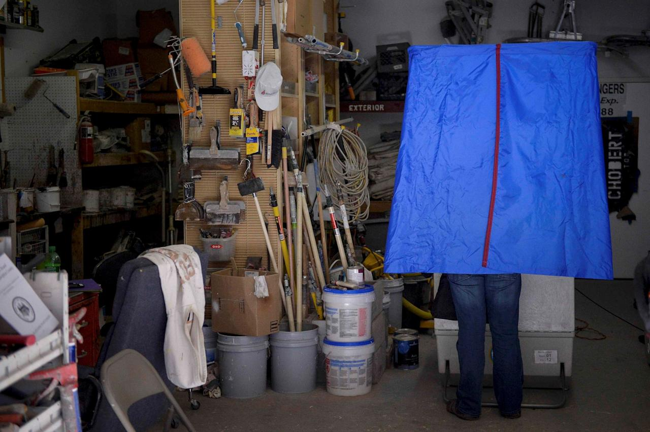 <p>A voter casts his ballot inside the garage of Chobert Decorators during the presidential election in Philadelphia, Pa., on Nov. 8, 2016. (Photo: Charles Mostoller/Reuters) </p>