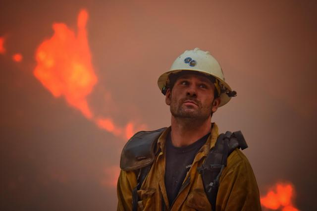 <p>County fire hand crew member Nikolas Abele keeps an eye on a hillside for any stray embers during a firing operation in Santa Monica Canyon in Carpinteria, Calif., Monday, Dec. 11, 2017. (Mike Eliason/Santa Barbara County Fire Department via AP) </p>