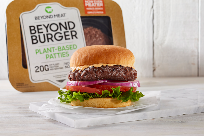 A Beyond Burger with cheese, with burgers in grocery-store packaging set behind it