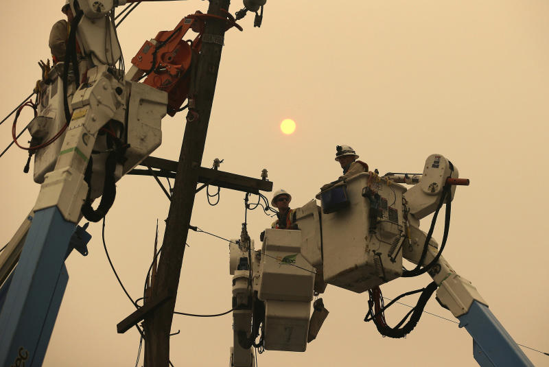 FILE - In this Nov. 9, 2018 file photo, Pacific Gas & Electric crews work to restore power lines in Paradise, Calif. Authorities say power outages have started Wednesday, Oct. 23, 2019, in Northern California after the state's largest utility said it was planning a widespread blackout citing wildfire danger. The Santa Rosa Fire Department tweeted Wednesday that shutoffs had started in the city and it was getting multiple reports of outages. Pacific Gas & Electric said earlier Wednesday it was going forward with blackouts later in the day that could affect 450,000 people in 17 counties of Northern California. (AP Photo/Rich Pedroncelli, File)