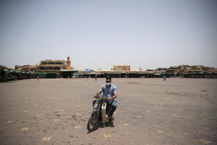 A motorcyclist rides his bike in the usually bustling but currently empty Marrakech landmark of Jemma el-Fnaa, Morocco, Wednesday, July 22, 2020. Morocco's restrictions to counter the coronavirus pandemic have taken a toll on the carriage horses in the tourist mecca of Marrakech. (AP Photo/Mosa'ab Elshamy)