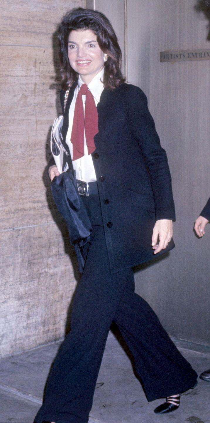 <p>Talk about power dressing. Jackie topped off her sleek black suit with a neck tie blouse and stylish belt. </p>