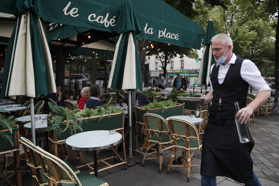 A waiter walks to serve customers at a restaurant, Monday, June 15, 2020 in Paris. Paris is rediscovering itself, as its cafes and restaurants reopen for the first time since the fast-spreading virus forced them to close their doors March 14. Restaurants outside the Paris region opened earlier this month, and Paris cafes were allowed to serve people outside but not open their doors. After three months of losses, some restaurateurs fear it will take a long time for business to come back. (AP Photo/Francois Mori)
