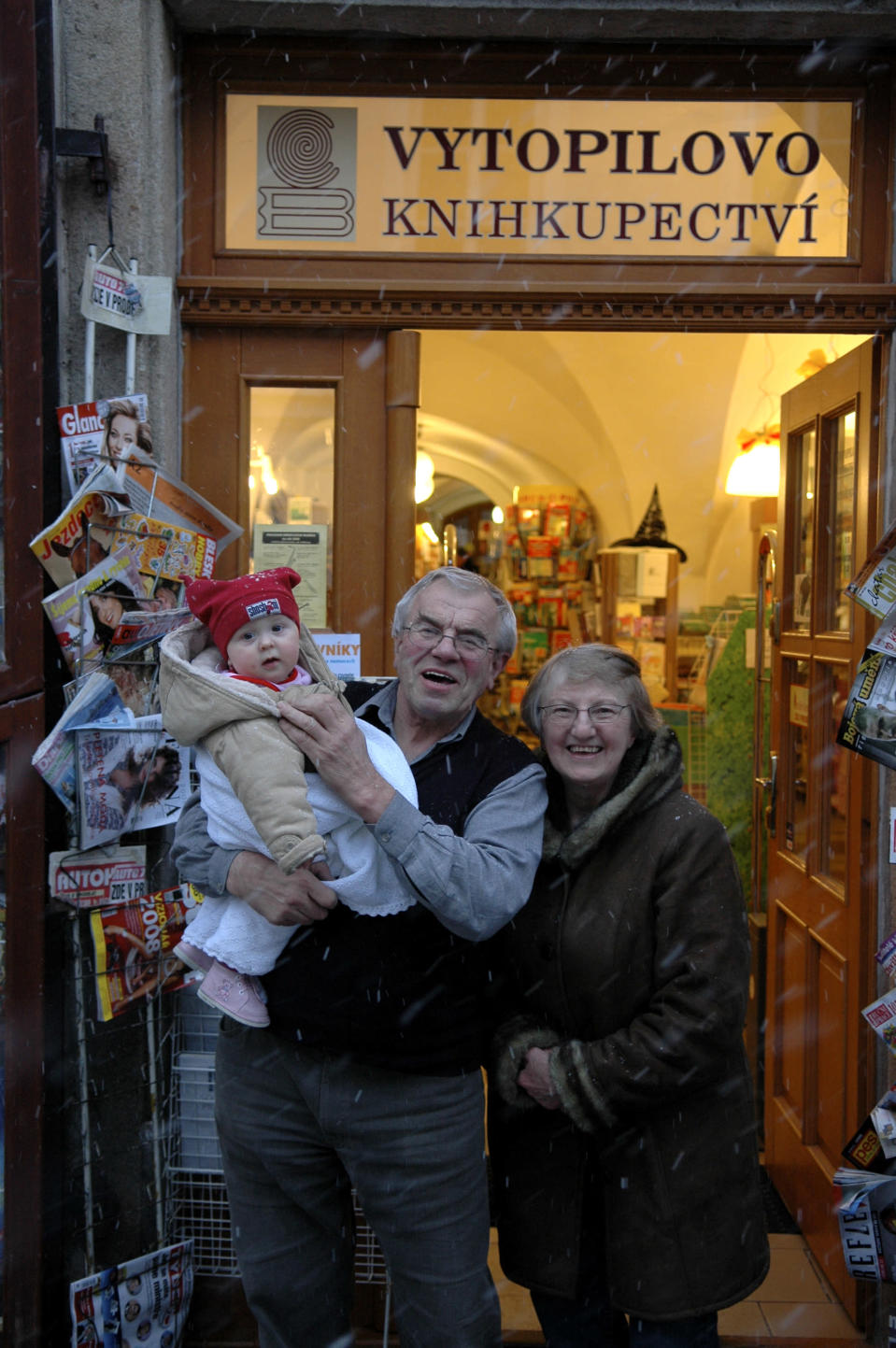 Jaromir Vytopil poses for a photo with a child in front of his bookstore in Pelhrimov, Czech Republic, Saturday, May 29, 2010. Some 25,000 have been killed by COVID-19 in the hard-hit Czech Republic. Jaromir Vytopil was one of them. His everyday presence in the small Czech town of Pelhrimov was something everybody took for granted for seven decades as he had served the generations of readers. The longest serving Czech bookseller, passed away on Nov 9. 2020, at age of 83. (AP Photo/Jan Vytopil)