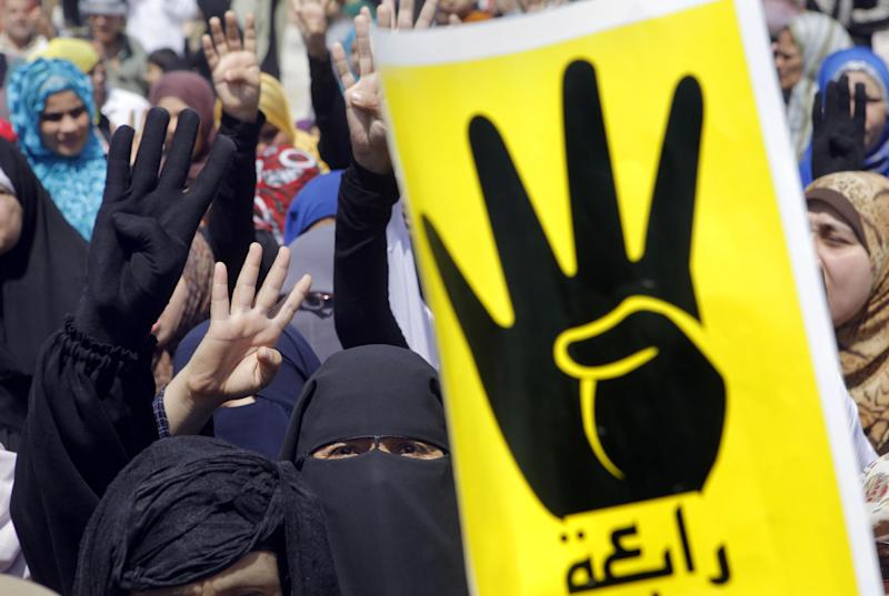 "Supporters of Egypt's ousted President Mohammed Morsi raise their hands and four fingers, as a symbol of the recent massacre in Rabaah al-Adawiya mosque on Aug. 14, during a march in old Cairo, Egypt, Friday, Aug. 23, 2013. Arabic reads, ""Rabaah."" Egyptian security and military forces deployed Friday around Cairo, closing off traffic in some major thoroughfares and in the city center ahead of protests by supporters of ousted President Mohammed Morsi. The rallies are a test of whether Morsi's supporters can keep up their pressure despite an intensive security crackdown on the Muslim Brotherhood, from which he hails. (AP Photo/Amr Nabil)"
