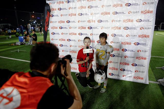 <p>Lisa Li, 9, of the Eagles gives a post-game interview after her team defeated the Sharklets in their Future League American football youth league match in Beijing, May 26, 2017. (Photo: Thomas Peter/Reuters) </p>
