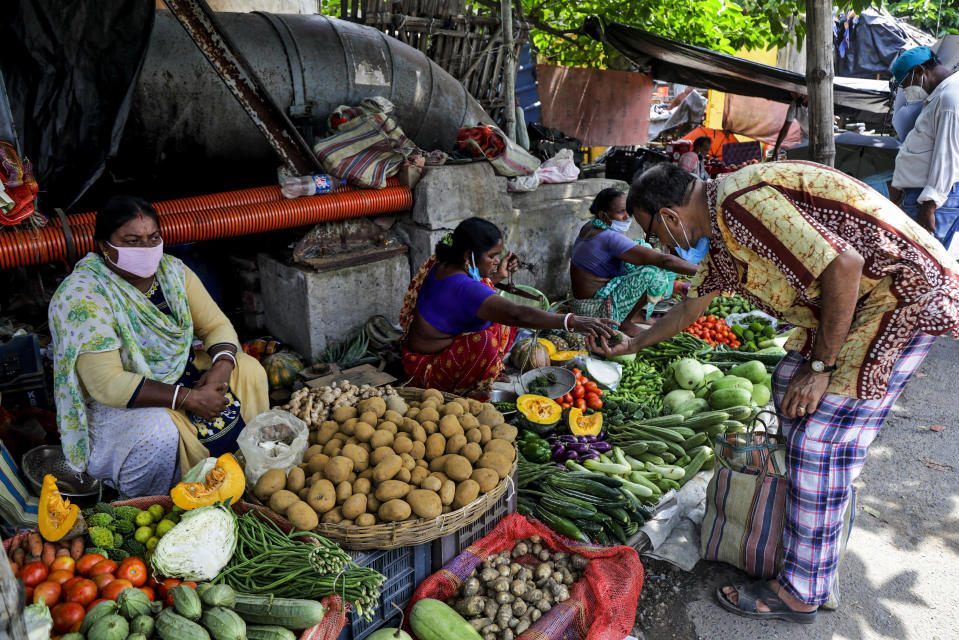Vendors wearing face masks as a precaution against the coronavirus sell vegetables at roadside stalls in Kolkata, India, Sunday, Aug. 2, 2020. India is the third hardest-hit country by the COVID-19 pandemic in the world after the United States and Brazil. (AP Photo/Bikas Das)