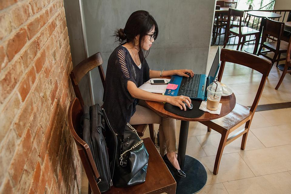 A young woman uses her laptop in a restaurant. (Photo: Omar Havana/Getty Images)