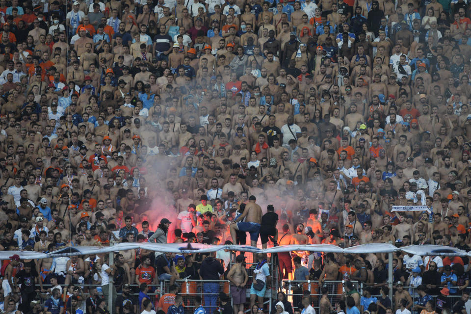 Marseille fans celebrate after Marseille's Bamba Dieng scored his side's opening goal during the French League One soccer match between Marseille and Rennes at the Velodrome stadium in Marseille, France, Sunday, Sept. 19, 2021. (AP Photo/Daniel Cole)