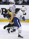 Boston Bruins left wing Marcus Johansson (90) goes airborne as he is sandwiched between Toronto Maple Leafs center Patrick Marleau (12) and defenseman Ron Hainsey (2) during the first period of Game 7 of an NHL hockey first-round playoff series, Tuesday, April 23, 2019, in Boston. (AP Photo/Charles Krupa)