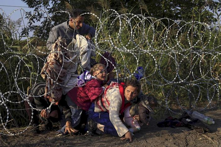 <p>Syrian migrants cross under a fence as they enter Hungary at the border with Serbia, near Röszke, Aug. 27, 2015. <i>(Bernadett Szabo/Reuters)</i></p>