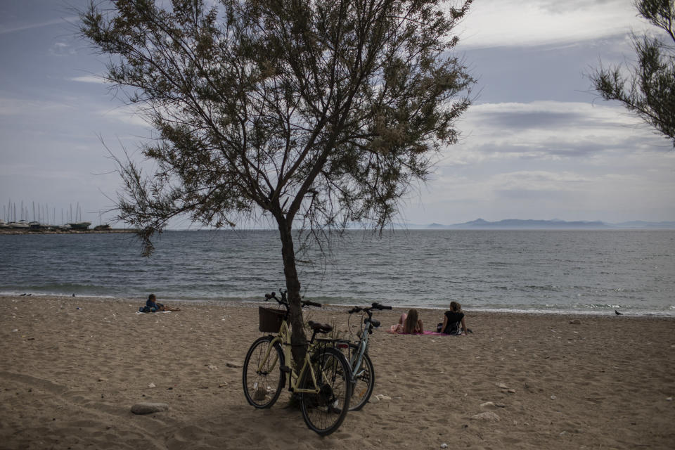 People sit a beach n Alimos, a seaside suburb of Athens, on Friday April 23, 2021. Easter holidays are often celebrated with relatives outside Athens and other cities, but the government has said COVID-19 infection levels remain too high to allow free travel.(AP Photo/Petros Giannakouris)