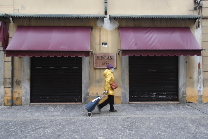 A woman walks in Codogno, Italy, Thursday, March 12, 2020. The northern Italian town that recorded Italy's first coronavirus infection has offered a virtuous example to fellow Italians, now facing an unprecedented nationwide lockdown, that by staying home, trends can reverse. Infections of the new virus have not stopped in Codogno, which still has registered the most of any of the 10 Lombardy towns Italy's original red zone, but they have slowed. For most people, the new coronavirus causes only mild or moderate symptoms. For some it can cause more severe illness. (AP Photo/Antonio Calanni)