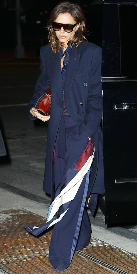 <p>Beckham stepped out in New York City in perfectly tailored flannel pants, a silk, see-through navy shirt, and a fabulous double-breasted cashmere wool overcoat. She hung a white and blue scarf from her wrist for added flare.</p>