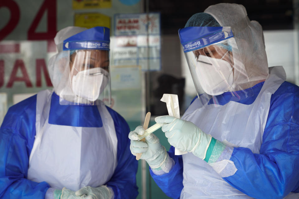 A clinic doctor checks sample for coronavirus testing after they collected it from a man on the outskirt of Kuala Lumpur, Malaysia, Tuesday, Oct. 6, 2020. The health ministry has warned that Malaysia is facing a new wave of virus cases as the outbreak has widened in recent days. New clusters have sprung up in many states amid increased travel to eastern Sabah state, a hotspot zone, for a state election last month. (AP Photo/Vincent Thian)