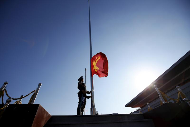 A North Korean soldier lifts a flag of the Workers' Party of Korea at the start of the parade celebrating the 70th anniversary of its founding in Pyongyang