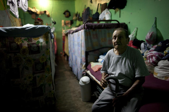 In this May 3, 2012 photo, inmate Jesus Hugo Hernandez, 85, sits in his bed inside his cell in San Pedro Sula Central Corrections Facility in San Pedro Sula, Honduras. Inside one of Honduras' most dangerous and overcrowded prisons, inmates operate a free-market bazaar, selling everything from iPhones to prostitutes. Guards do not cross into the inner sanctum controlled by prisoners, and prisoners do not breach the perimeter controlled by guards. (AP Photo/Rodrigo Abd)