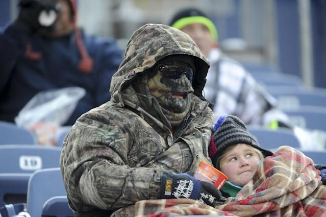 Fans try to stay warm before an NFL football game between the Denver Broncos and the Tennessee Titans Sunday, Dec. 8, 2013, in Denver. (AP Photo/Chris Schneider)