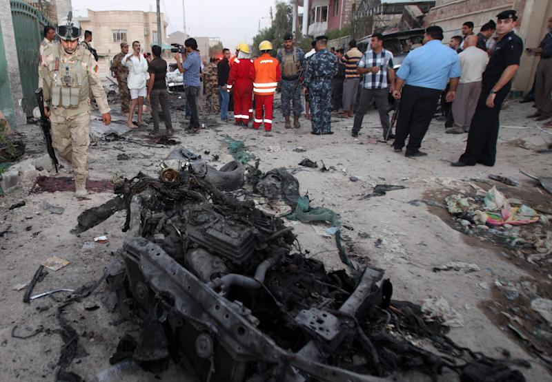 In this picture taken on Sunday, July 14, 2013, security forces inspect the scene of a car bomb attack in Basra, Iraq. Ramadan is shaping up to be the deadliest in Iraq since a bloody insurgency and rampant sectarian killings had the country teetering on the edge of civil war more than half a decade ago. (AP Photo/ Nabil al-Jurani)