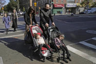 An ultra-Orthodox Jewish man and woman wheel strollers with sleeping children in them as they cross a street on the Jewish joldiay of Sukkot, Sunday, Oct. 4, 2020, in the Borough Park neighborhood of Brooklyn in New York. New York City's mayor said Sunday that he has asked the state for permission to close schools and reinstate restrictions on nonessential businesses in several neighborhoods, including Borough Park, because of a resurgence of the coronavirus. (AP Photo/Kathy Willens)
