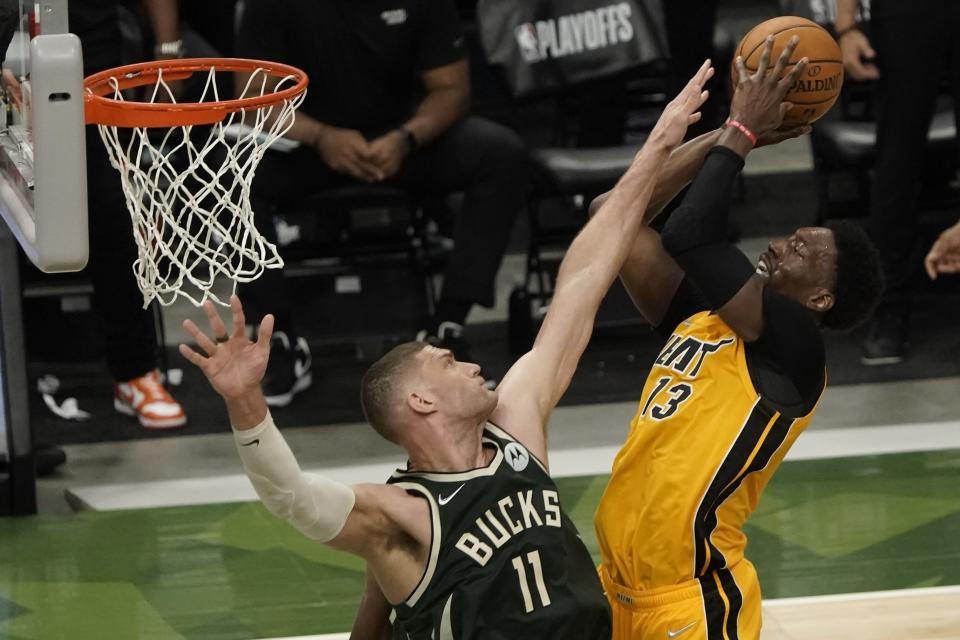 Miami Heat's Bam Adebayo shoots over Milwaukee Bucks' Brook Lopez during the first half of Game 1 of their NBA basketball first-round playoff series Saturday, May 22, 2021, in Milwaukee. (AP Photo/Morry Gash)