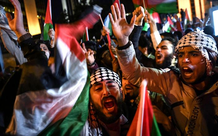 Protesters chant slogans and wave Palestinian flags during a protest against Israel in front of the Israeli Consulate in Istanbul, late on May 10, 2021 - OZAN KOSE/AFP